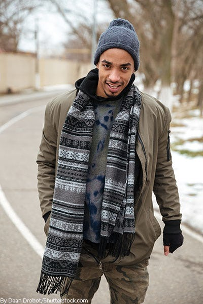 Young man wearing an army green coat with a knit scarf 583cd79e91b3