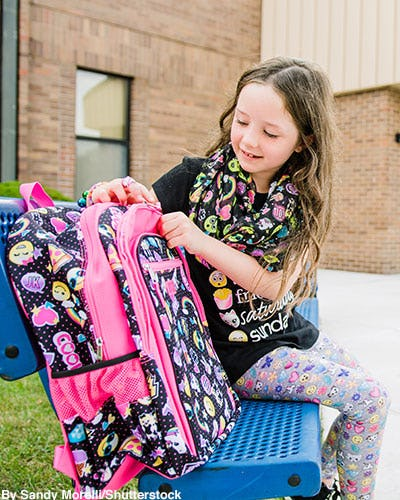 Girl opening an emoji patterned backpack.