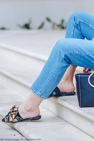 Woman sitting on steps wearing blue jeans and a long green flowy jacket paired with navy blue floral velvet mules
