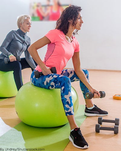 Woman exercising on a yoga ball with free weights.