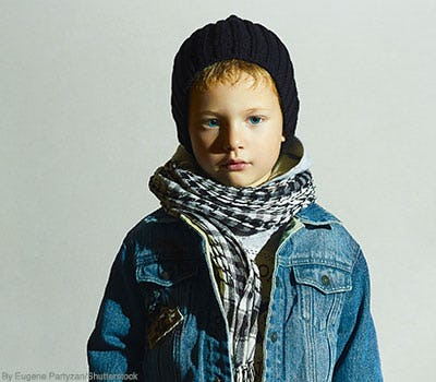 Little boy wearing denim jacket and checkered scarf and beanie hat.
