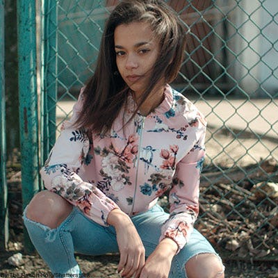 Fashionable teen girl wearing ripped jeans and a floral bomber jacket.