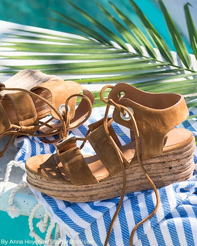 Brown suede wedge sandals laying by the pool on a stripe blue towel.