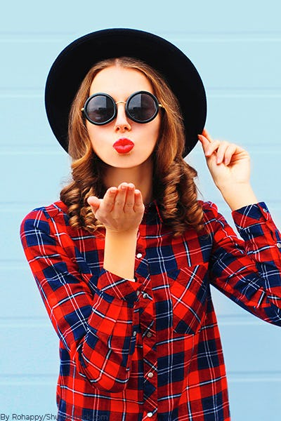 Young woman wearing a red plaid shirt with a black hat