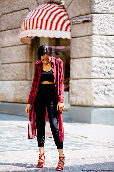 Stylish woman wearing a black cutout jumpsuit, red strappy sandals, and a red and blue sheer plaid kimono.