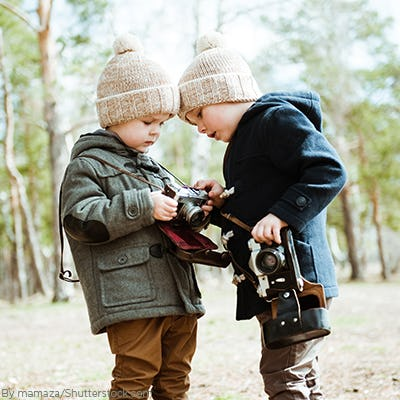 Two young boys in the woods wearing trending anorak jackets and matching beanies