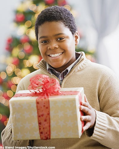 Boy holding a holiday gift wearing a beige half-zip sweater.