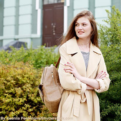 Woman wearing trench coat in fall.