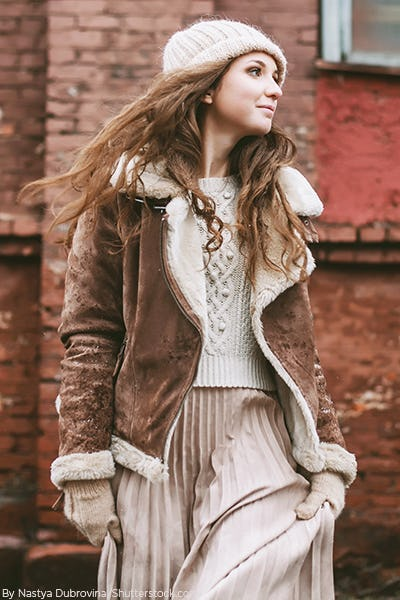 Woman wearing a white knit sweaters with a white pleated skirt, white beanie and brown suede moto jacket