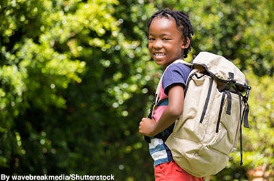 Boy wearing a rugged outdoorsy backpack.