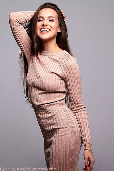 Woman wearing blush ribbed sweater dress.