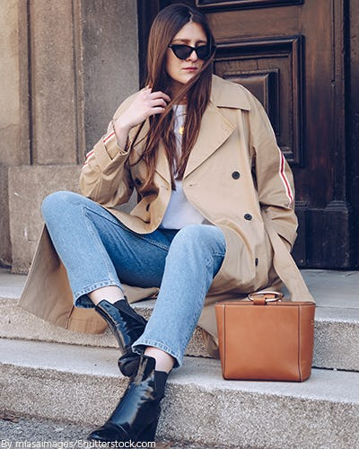 Young woman sitting on steps wearing a camel trench coat with blue jeans and black booties