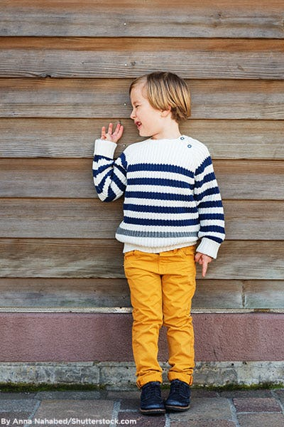 Little boy wearing mustard yellow chinos, striped sweater, and black shoes.