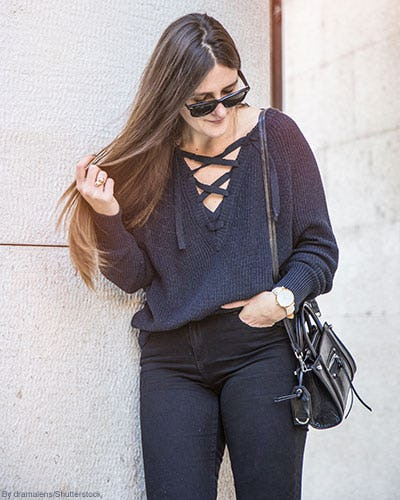 Woman wearing lace-up navy sweater, black skinny jeans, and a black cross-body purse.