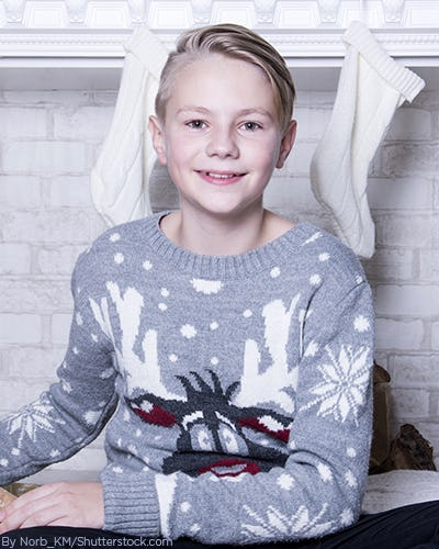 Young boy wearing a christmas sweater with a reindeer and snowflakes on it