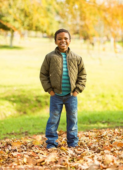Little boy wearing quilted olive bomber jacket in fall.
