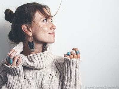 Woman wearing chunky cable knit neutral sweater and turquoise rings.