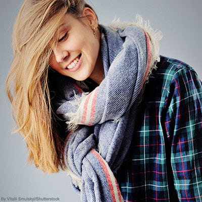 Woman wearing a plaid men's shirt and a thick fall scarf.