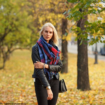 Woman outside in the autumn wearing a plaid blanket scarf, a black leather jacket, and black skinny jeans.