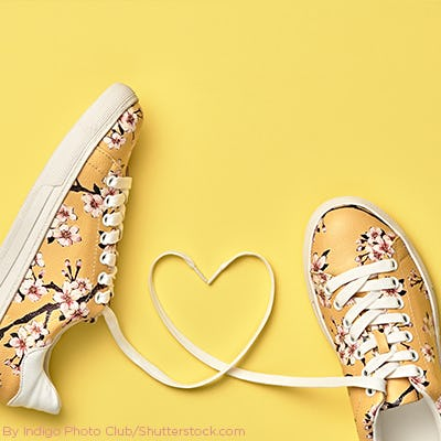 Yellow floral print shoes with shoelaces in the shape of a heart.