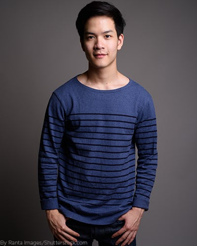 Young asian man wearing a blue sweater with black pinstripes and black jean