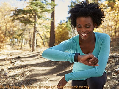 Woman exercising outdoors with smartwatch.