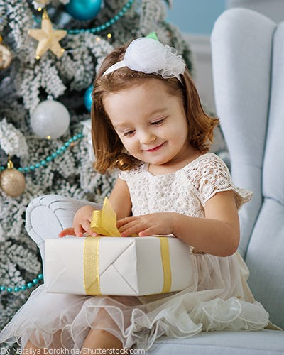 Little girl sitting on a chair in front of a christmas tree opening a present wearing a white dress and matching headband