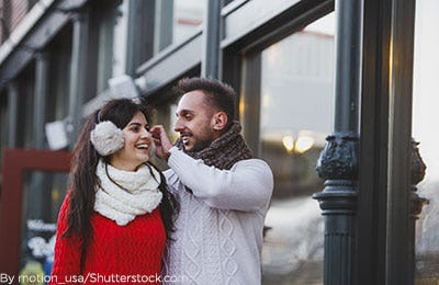 Man helping woman with her earmuffs.