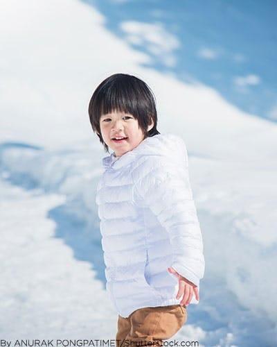 Little boy wearing white puffer jacket.