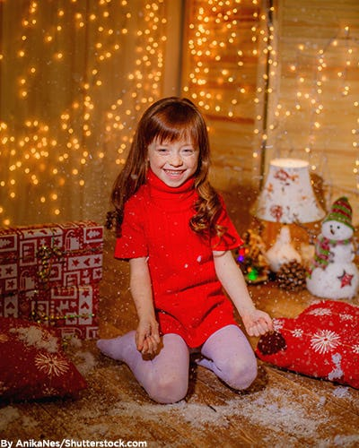 Little girl in a red holiday sweater dress.