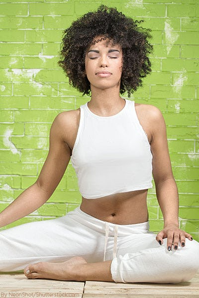 Woman on yoga mat wearing a white crop top and white leggings