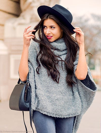 Woman wearing a gray poncho sweater and a black wool hat while carrying a black leather handbag.