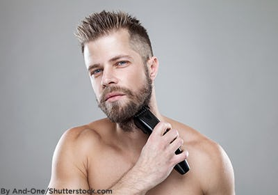 Man trimming his beard with an electric beard trimmer.