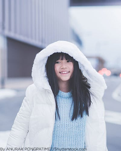 Little girl wearing white puffer jacket and pastel blue sweater.