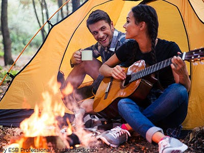 A couple camping outdoors together