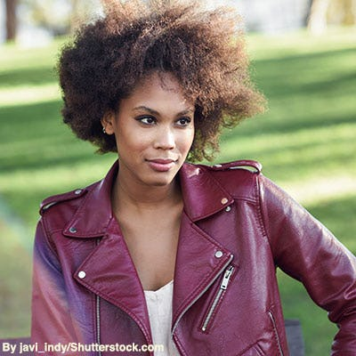 Stylish woman wearing a burgundy leather moto jacket with zippers.