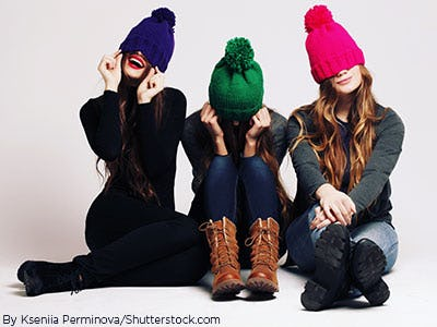 Three young ladies sitting on a white background with colored beanies and boots