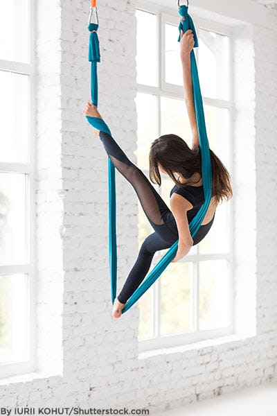 Woman practicing acrobatic exercise in mesh leggings.