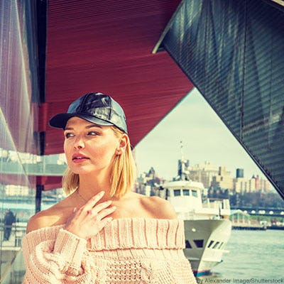 Woman wearing a black leather baseball cap and a pale pink off-the-shoulder sweater.
