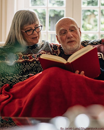 Older couple sitting on the couch read a book together