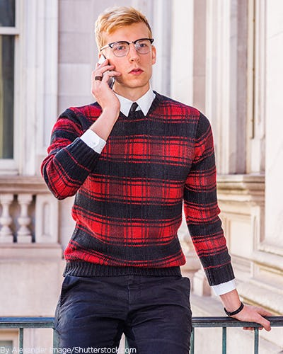Young man on his phone wearing a black and red plaid sweater with black pants
