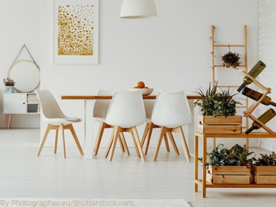 A long wooden table with white acrylic chairs