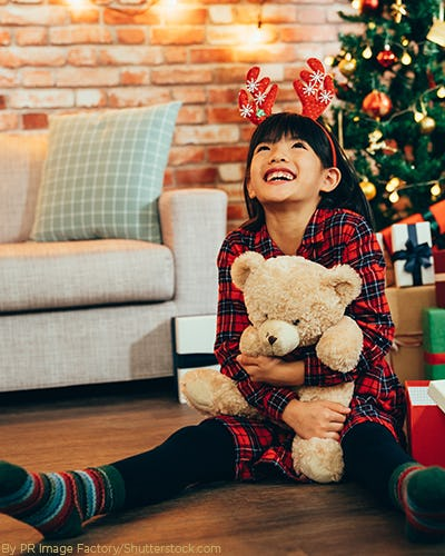 Young girl wearing a red plaid dress sitting on the ground in front of the christmas tree