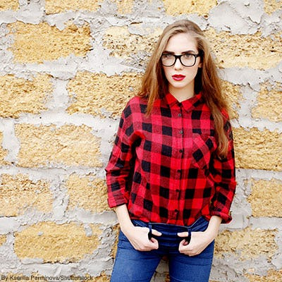 Woman posing in front of a stone wall wearing glasses and a black and red buffalo check shirt tucked into blue jeans.