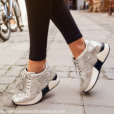 Woman wearing metallic silver dad sneakers and black leggings.