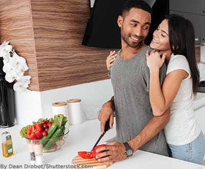 Man cooking in his kitchen with his wife.
