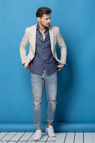 Man wearing distressed denim jeans, a navy button up and a tan blazer