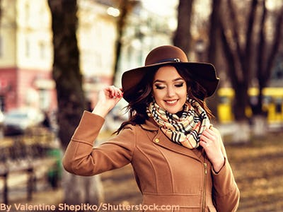 Fashionable woman in a camel coat, brown floppy hat, and plaid scarf.