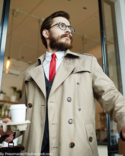 Young man wearing a tan trench coat while holding coffee