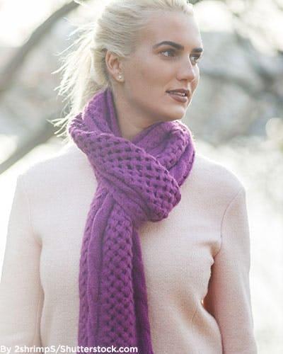 Woman wearing purple knit scarf in winter.